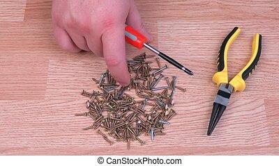 Man sorting metal screws