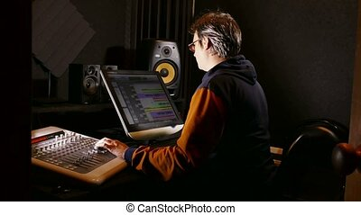 man sound designer in his recording studio - tracking shot -...