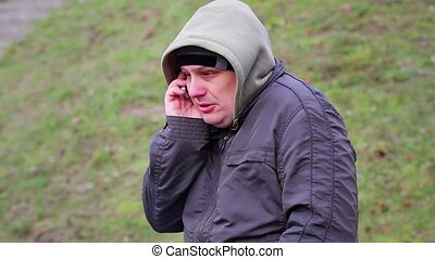Man speaking on the cell phone at outdoors in cold weather