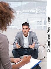 Man speaking to a therapist while she is taking notes