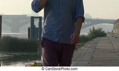 Man Speaks by a Mobile. His Body And Hands Are Seen, on the Riverbank in Slo-Mo