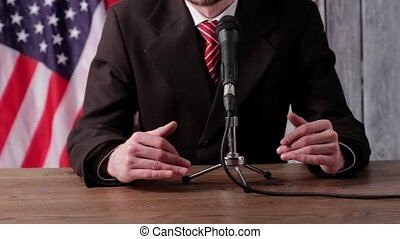 Man speaks into microphone. American flag behind businessman...