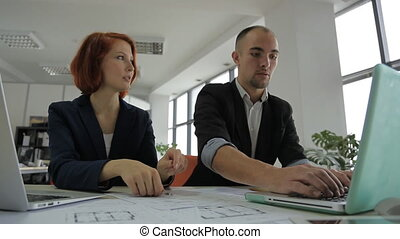 man specialist consultant works with your boss woman in a large, bright office.