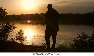 Man spends his leisure in nature and fishes at sunset