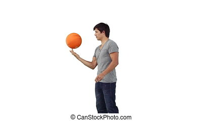 Man spinning a basketball on his finger against a white...