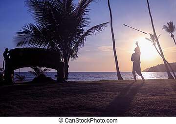 Man spinning contact staff or stick on the beach with sunrise