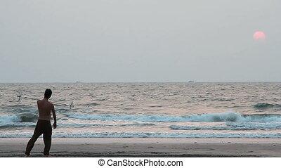 man spinning pole on the beach. - Goa, India - February 10,...