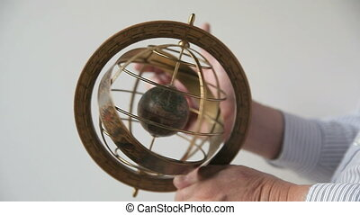 a man holds and spins a model of an armillary sphere