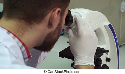 Man spins coarse adjustment knob on microscope at the laboratory