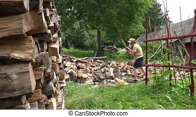 man split wood with axe in one after other wooden log yard....