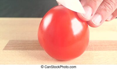 Man splitting ripe red tomato with white knife. Close up...