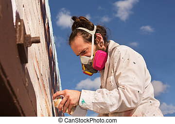 Man Spray Painting - Graffiti artist with respirator spray...
