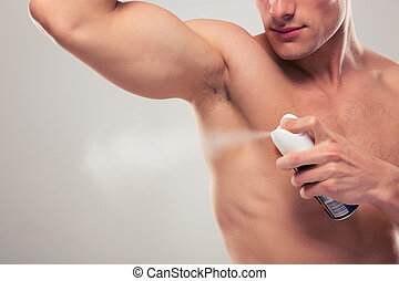 Man spraying deodorant over gray background
