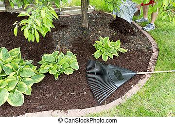 Man spreading mulch in the garden