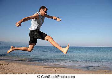 man springend, op het strand