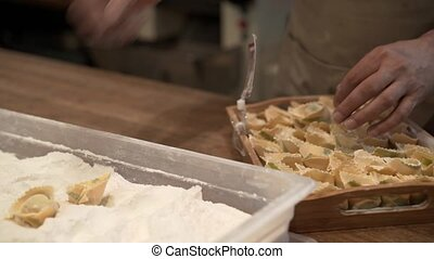 Man sprinkling tortellini with flower and putting them in a...