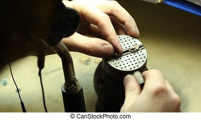 Man squeezed in vise two gold rings begin processing