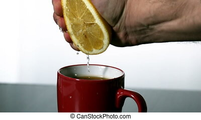 Man squeezing lemon into red mug in slow motion