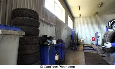 Man stacking worn tires in garage. tire changing and storing services.