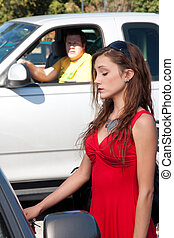 Young pretty woman in bright red dress unlocks her car door as a man watches stalking in the background from his pickup truck.