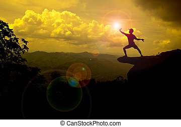 man stand on mountain trying to catch the Sun