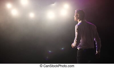Man stand up comedian speaking jokes in micropphone headset on stage, back view.
