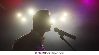 Man stand up comedian telling funny jokes in micropphone standing on stage.
