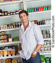 Man Standing Against Shelves In Store