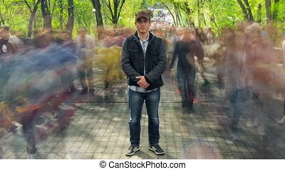 Man standing alone in blurred crowd, on background green trees. Time Lapse