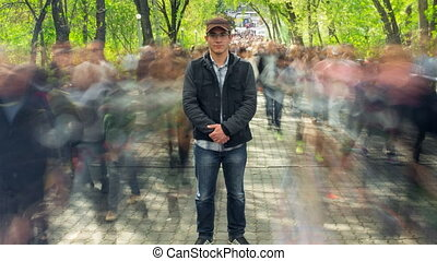Man standing alone in blurred crowd, on background green trees. Time Lapse. The camera is approaching