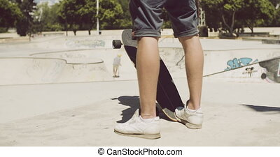 Man standing at a skate park with his longboard