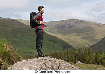 Man standing at hill top admiring the view after a hike in...