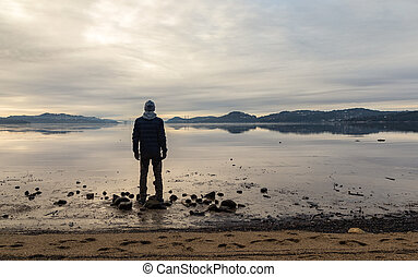 Man standing at the beach, looking at the calm sea and the mist and fog. Hamresanden, Kristiansand, Norway
