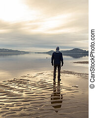 Man standing at the beach, reflections of the man in the water. Calm sea, mist and fog. Hamresanden, Kristiansand, Norway