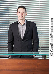Man standing behind reception desk