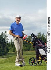 Man standing by golf bag full of sticks