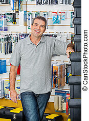 Man Standing By Stacked Toolboxes In Store