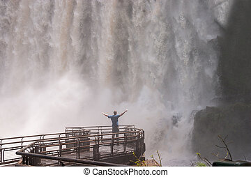 Man standing close to the Iguacu Falls hands up Power symbol
