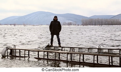 Man standing dangerously on a narrow icy pier on the river...