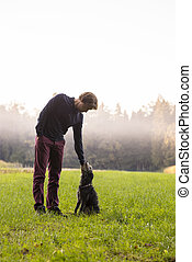 Man standing enjoying nature as he bends down to his dog to...