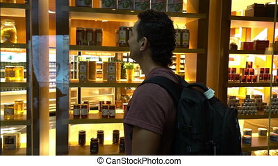 man standing in front of shop window store in airport teminal