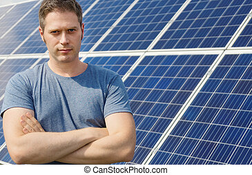 Man standing in front of solar panels. Renewable energy.