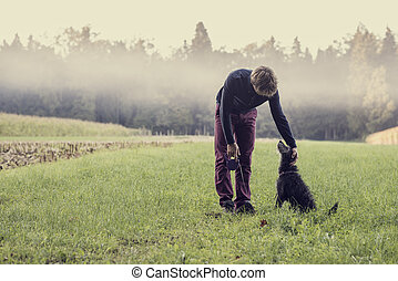 Man standing in green grassland bending down to pat his...