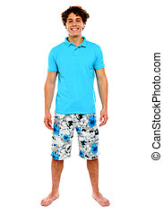 Man standing in shorts with smile on his face. Isolated