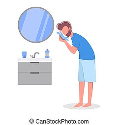Man standing in the bathroom wiping his face with a towel.