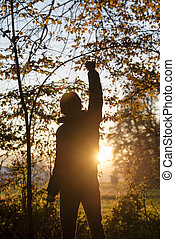 Man standing in the woods facing a setting sun