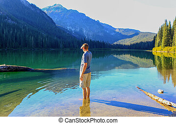 Man standing in water with feet and looking at mountain