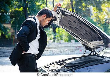 Man standing near broken car with open hood