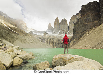 man standing near lake in patagonia, torres del paine