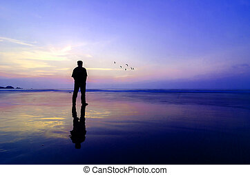 Man standing near the beach looking at sun rising